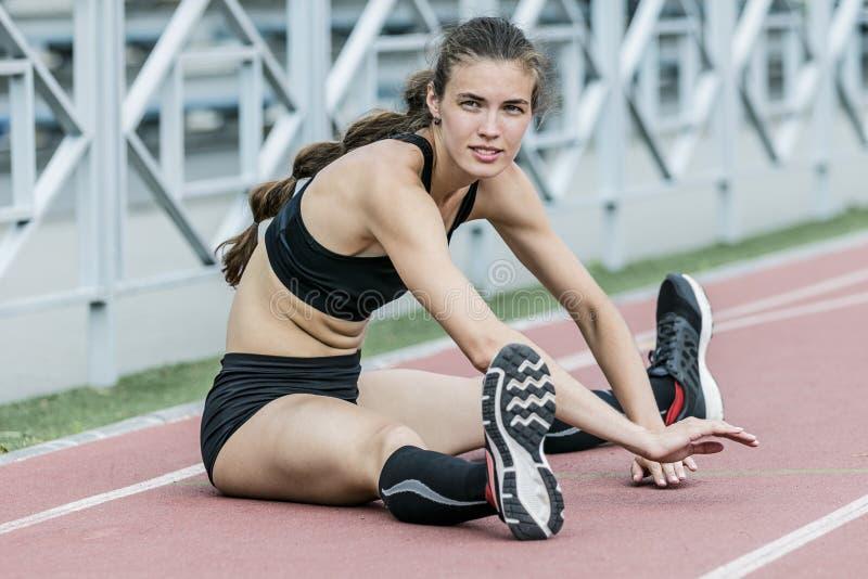 Sportflicka som gör sträcka övning i stadion arkivfoto