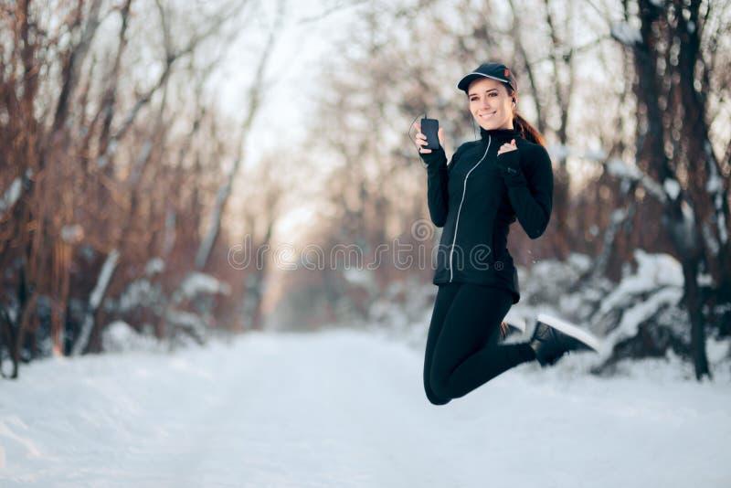 Sportflicka som lyssnar till musik som hoppar i vintertid royaltyfri bild