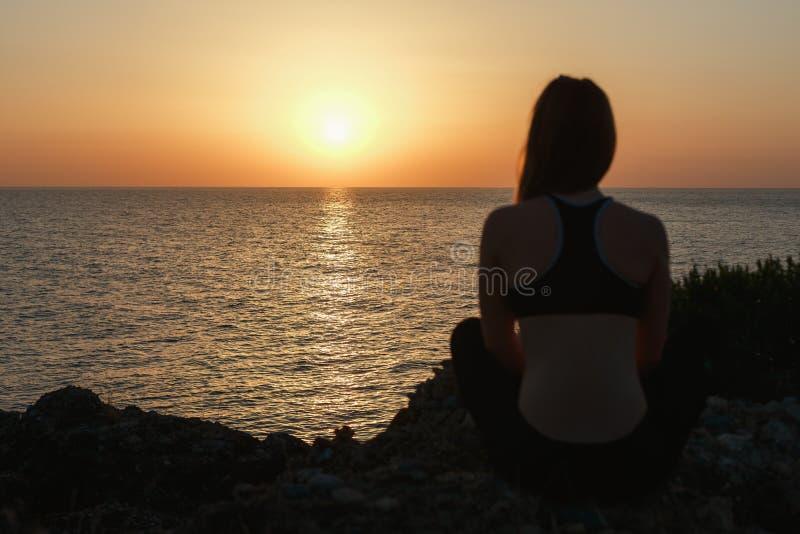 Sportflicka som mediterar vid havet på solnedgången arkivfoto