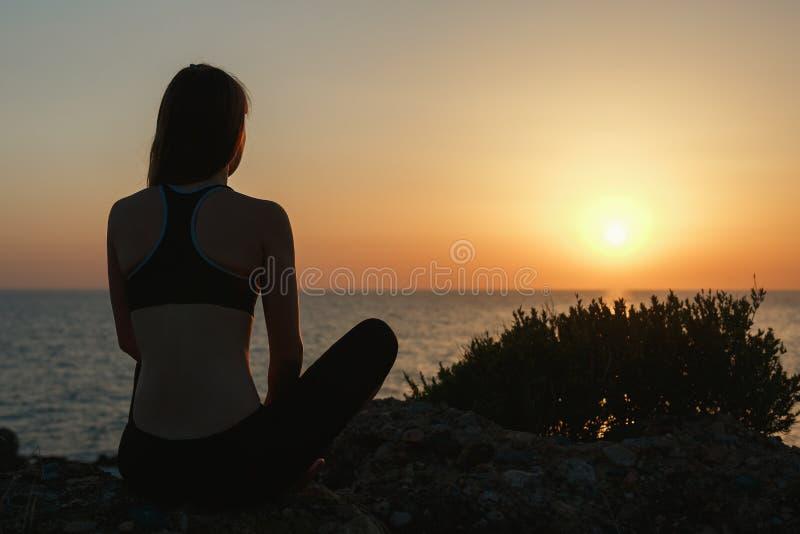 Sportflicka som mediterar vid havet på solnedgången royaltyfria bilder