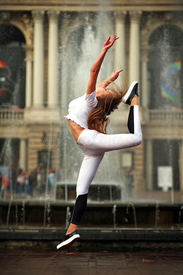 Sportflickagymnast som i flykten hoppar på gatan av den gamla staden royaltyfria bilder