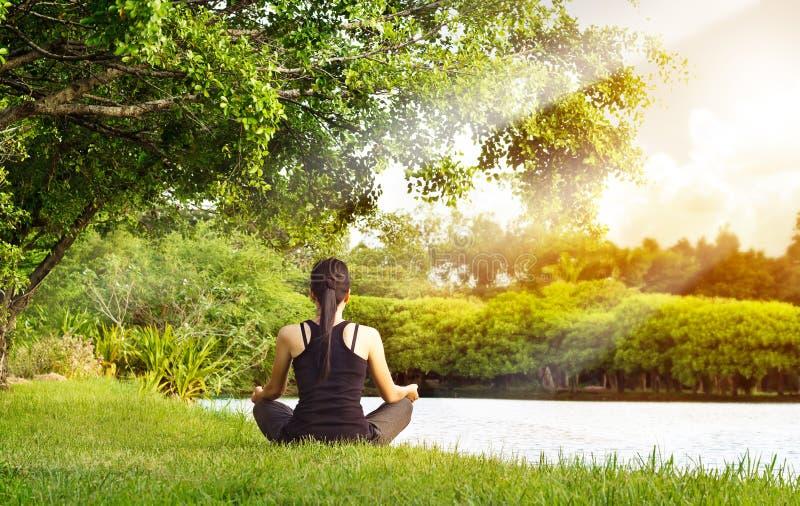 Sportflickan som mediterar i naturgräsplan, parkerar på soluppgången royaltyfria foton