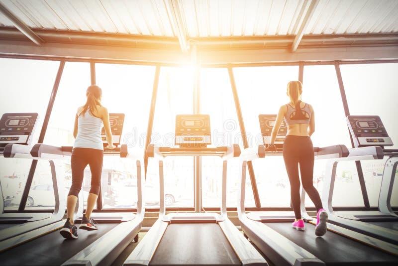 Sportflickor som kör på trampkvarnen i konditionidrottshall på soluppgång arkivbilder