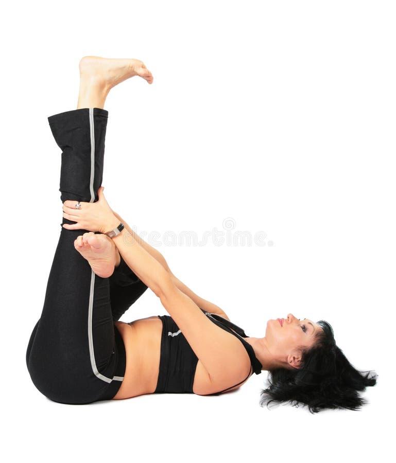 Sportfrau bildet innen Übung mit dem Fahrwerkbein oben stockfoto