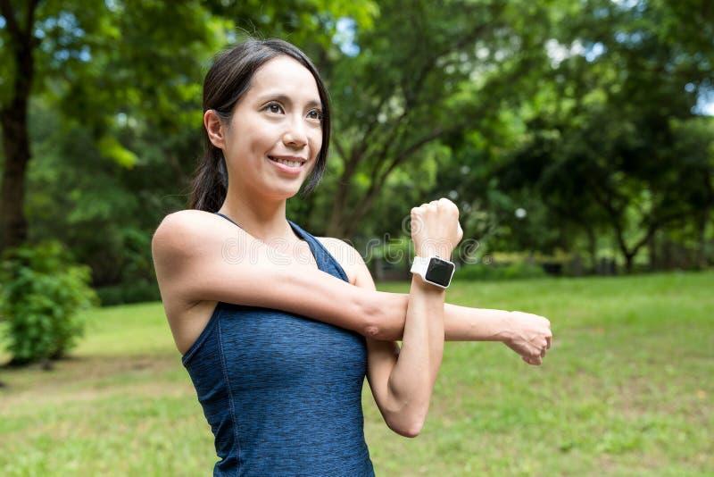 Sportfrau, die Arm im Park skizziert lizenzfreie stockbilder