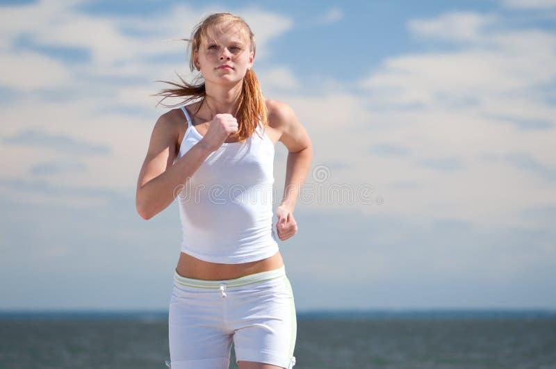 Sportfrau, die auf Strand läuft stockbild