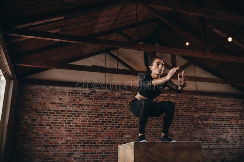 Sportfrau, die einen Kastensprung an der Turnhalle tut lizenzfreie stockfotos
