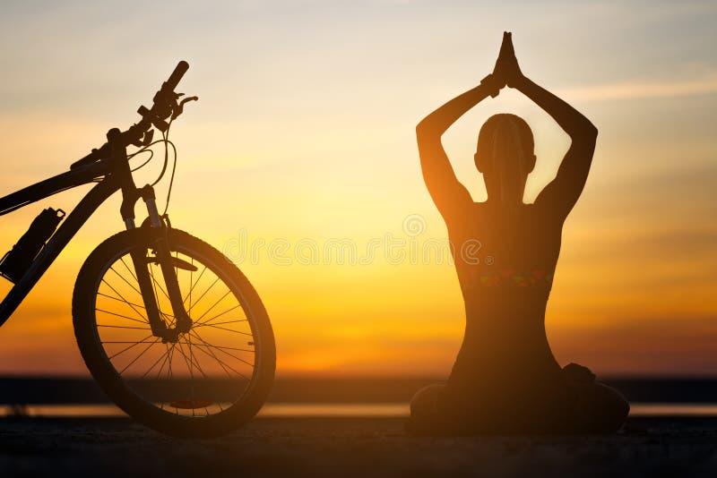 Sportfrau, die Yoga bei Sonnenaufgang auf dem Seestrand vor dem hintergrund des orange Himmels und des Fahrrades tut Entspannung  lizenzfreie stockbilder