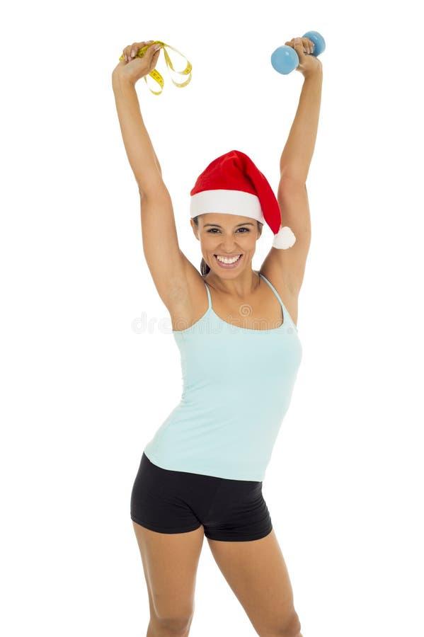 Sportfrau im Sankt-Weihnachtshut, der Gewichtsdummköpfe und Maßband hält stockbild