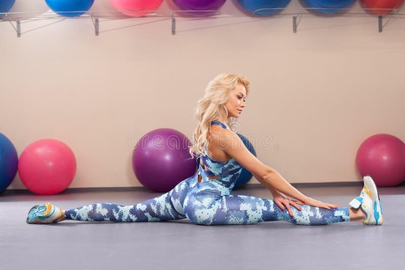 Sportfrau sitzt auf einer Schnur Athletisches Mädchen, das Übung im Eignungsraum ausdehnend tut Aktiver Lebensstil lizenzfreies stockbild