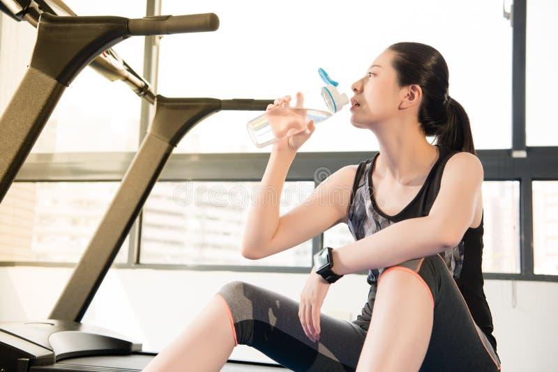 Sportfrauenrest auf Tretmühlengebrauch smartwatch Trinkwasser stockfotografie