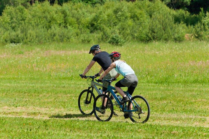 Sportgebirgspaare, die sonnige Wiesen radfahren lizenzfreie stockbilder