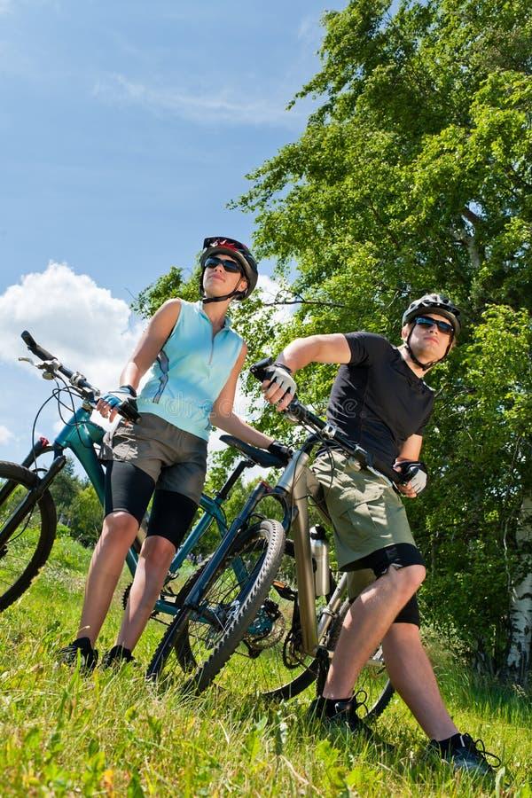 Sportgebirgsradfahrende Paare entspannen sich in den Wiesen lizenzfreie stockfotografie