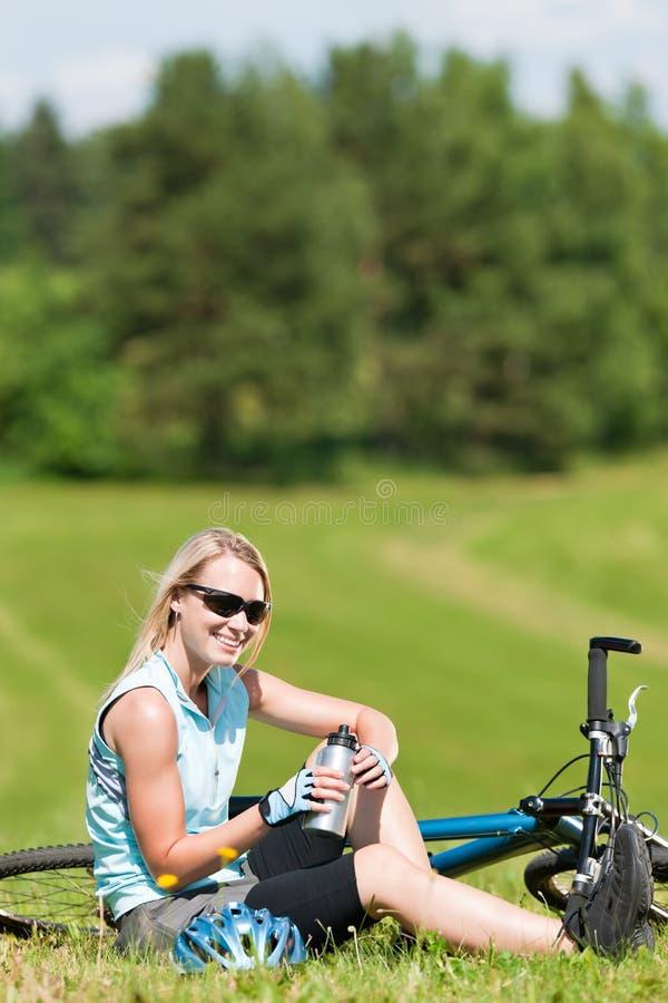 Sportgebirgsradfahrendes Mädchen entspannen sich in den Wiesen lizenzfreie stockfotografie