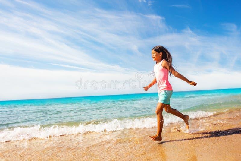 Sportief Aziatisch meisje die langs zandig strand lopen royalty-vrije stock foto
