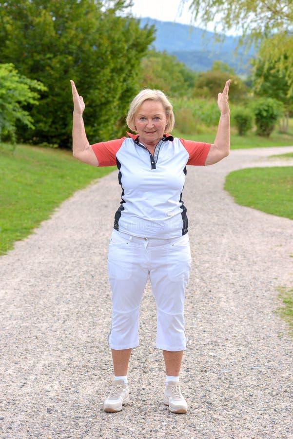 Sportief bejaarde die sportoefeningen doen stock foto