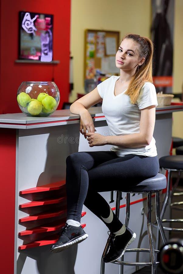 Sportief blonde op een barstoel in een geschiktheidsstudio stock afbeeldingen
