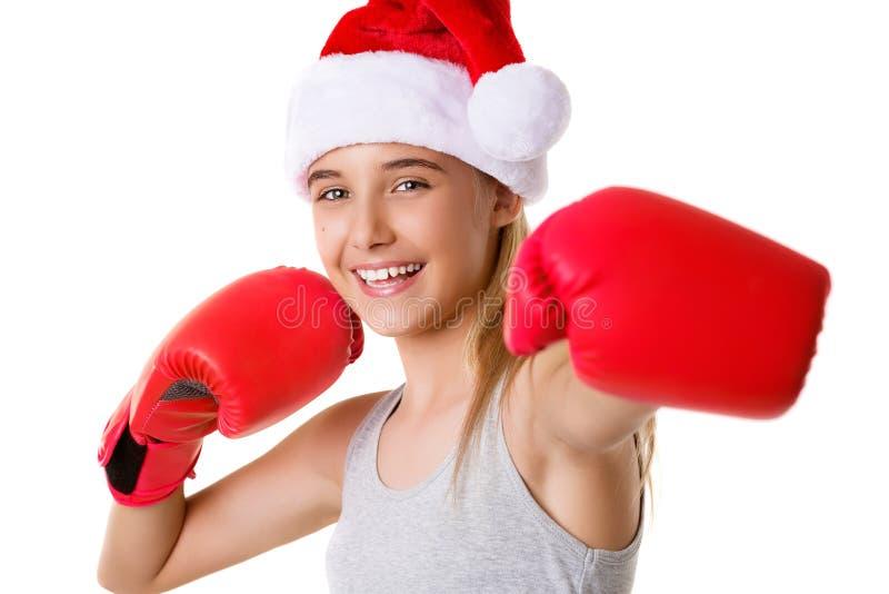 sportief gelukkig jong meisje die de hoed van Kerstmissanta met het bestrijden van geïsoleerde handschoenen dragen royalty-vrije stock afbeeldingen