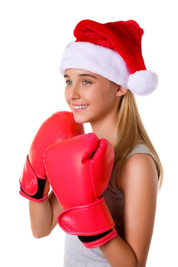Sportief gelukkig jong meisje die de hoed van Kerstmissanta met het bestrijden van geïsoleerde handschoenen dragen, stock foto's