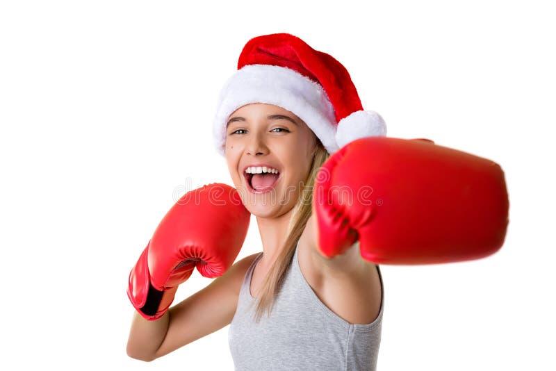 sportief gelukkig jong meisje die de hoed van Kerstmissanta met het bestrijden van geïsoleerde handschoenen dragen stock afbeelding