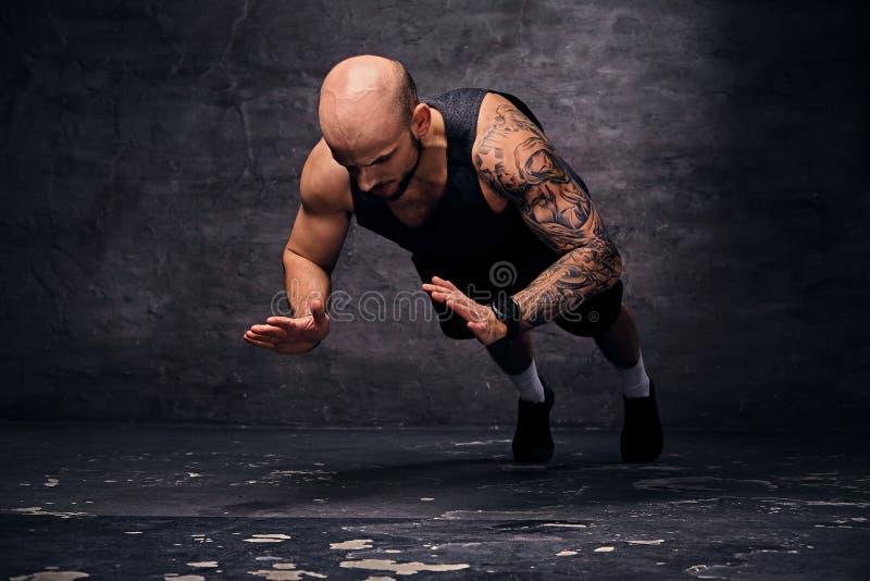 Sportief geschoren hoofd sportief mannetje die duw UPS met sprongen doen stock foto