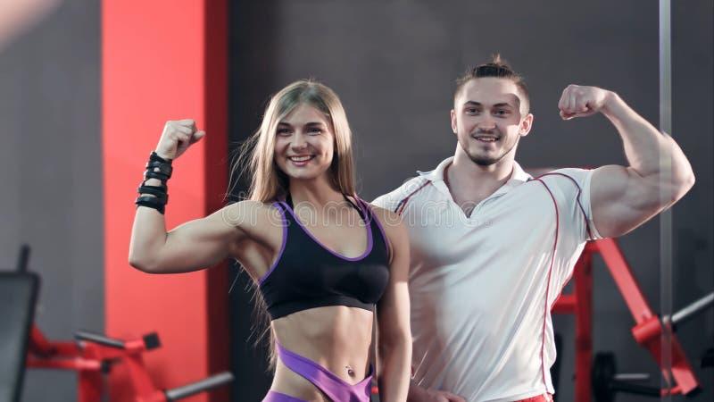 Sportief jong paar die en met hun bicepsen stellen pronken royalty-vrije stock foto's