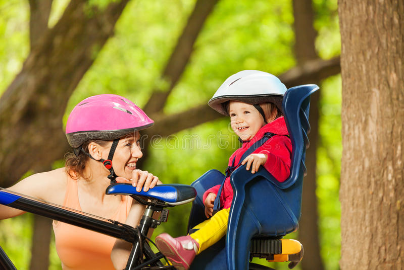Sportief mamma en haar kind, die in fietszetel zitten stock fotografie