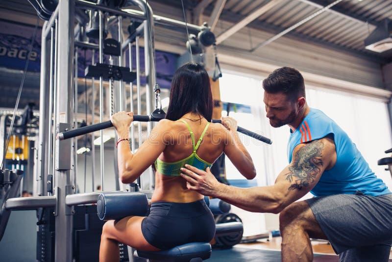 Sportief meisje die gewichtsoefeningen met hulp van haar persoonlijke trainer doen bij gymnastiek royalty-vrije stock foto's