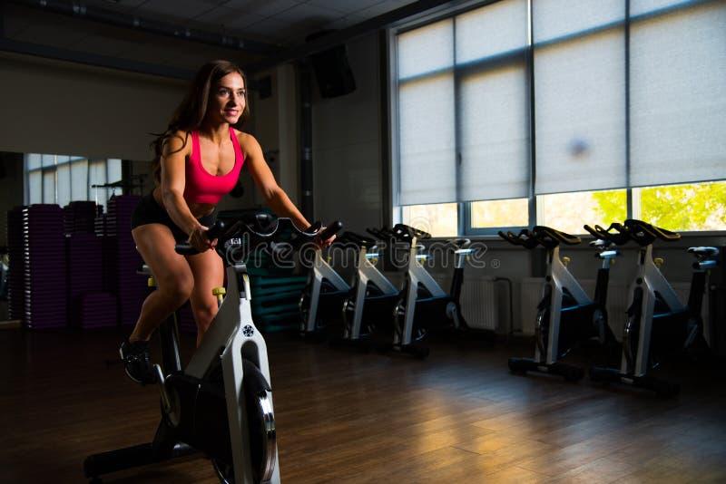 Sportief meisje in geschiktheidszaal op cyclus stock foto's