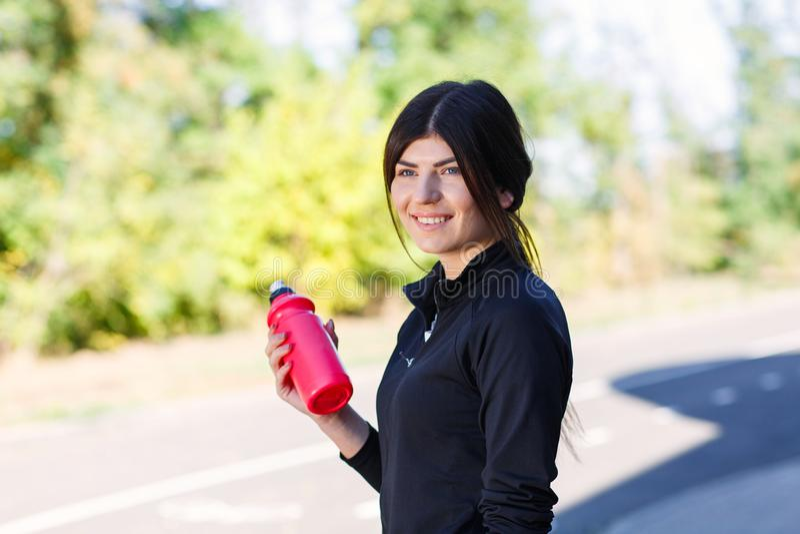 Sportief meisje met een fles voor water op de straat openlucht royalty-vrije stock fotografie
