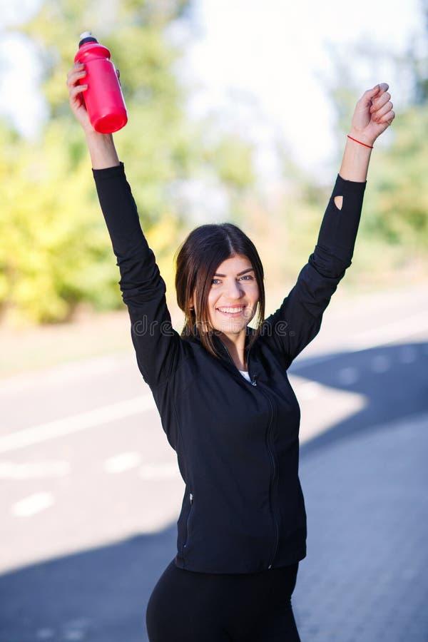 Sportief meisje met een fles voor water op de straat openlucht royalty-vrije stock afbeeldingen
