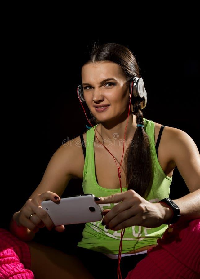 Sportief meisje met hoofdtelefoons het luisteren muziek op grijze achtergrond De jonge vrouw met vlecht, draagt groene T-shirt, b royalty-vrije stock foto's