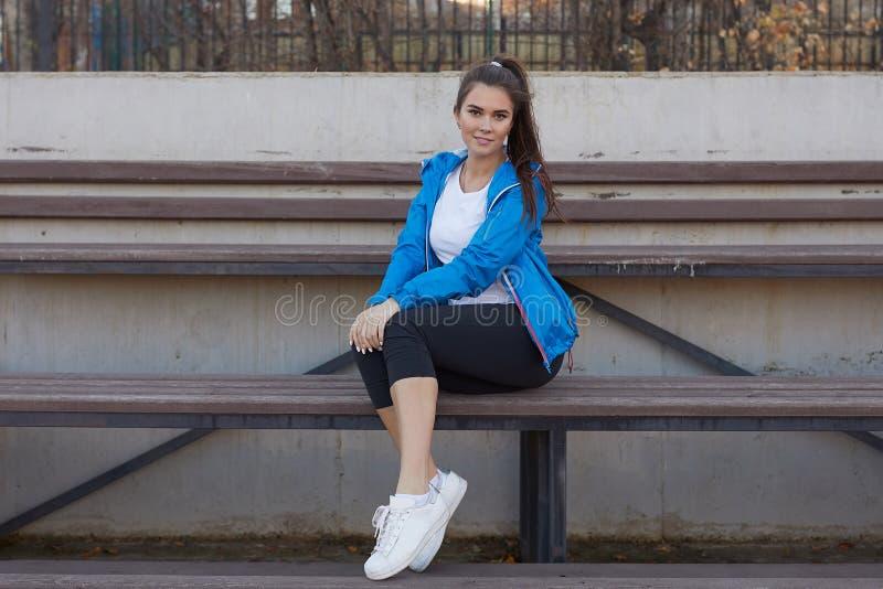 Sportief meisje op het stadion Stadiontribune Slanke sportieve geschiktheidsvrouw stock afbeeldingen