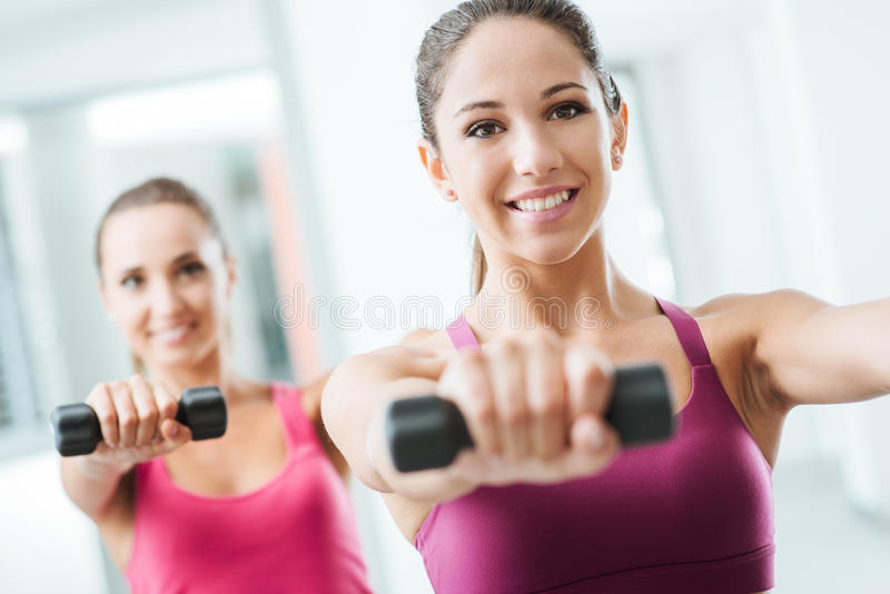 Sportief meisjesgewichtheffen bij gymnastiek stock fotografie