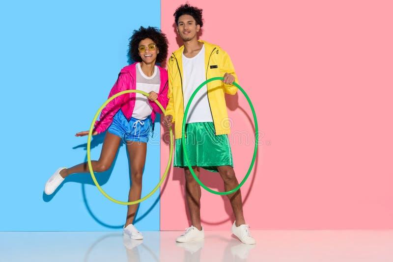 Sportief paar die zich met hoepels bevinden en aan camera op roze en blauw kijken stock fotografie