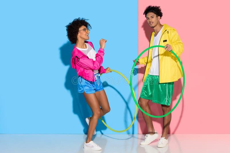 Sportief paar die zich met hoepels op roze en blauw bevinden stock afbeelding