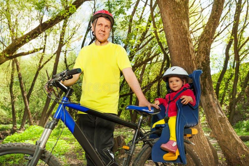 Sportief personenvervoer zijn kleine dochter in fietszetel royalty-vrije stock afbeeldingen