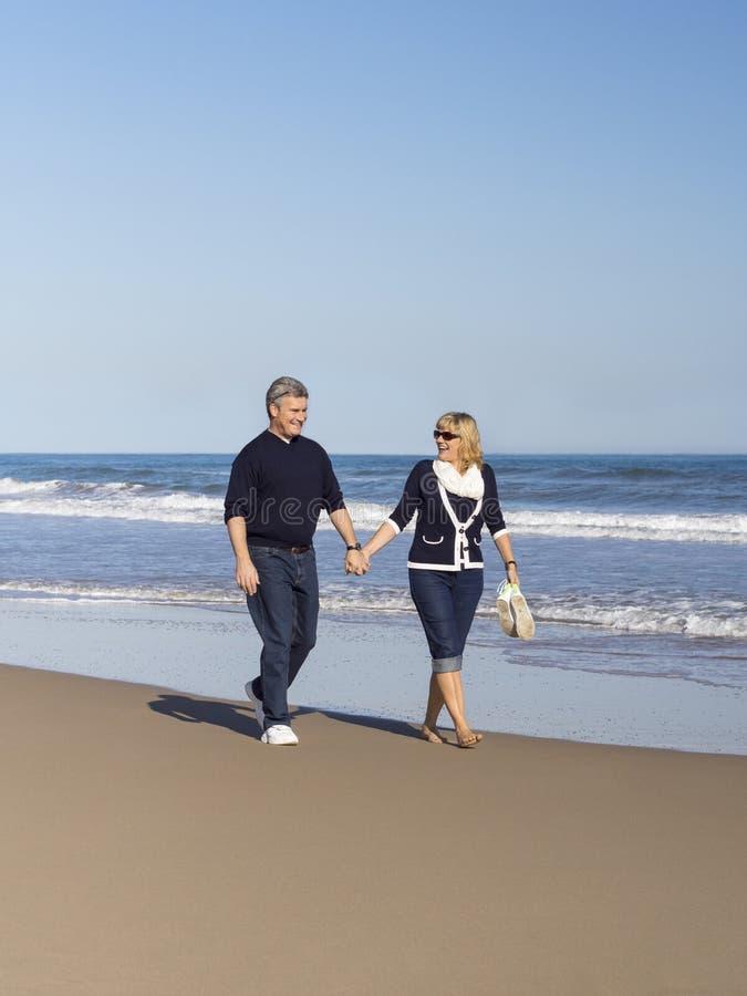 Sportief rijp paar die langs het strand lopen stock afbeelding