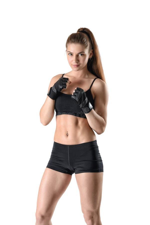 Sportief spiergeschiktheidsmeisje dat haar vuisten dichtklemt die zwarte handschoenen in verdedigingshouding dragen stock foto's