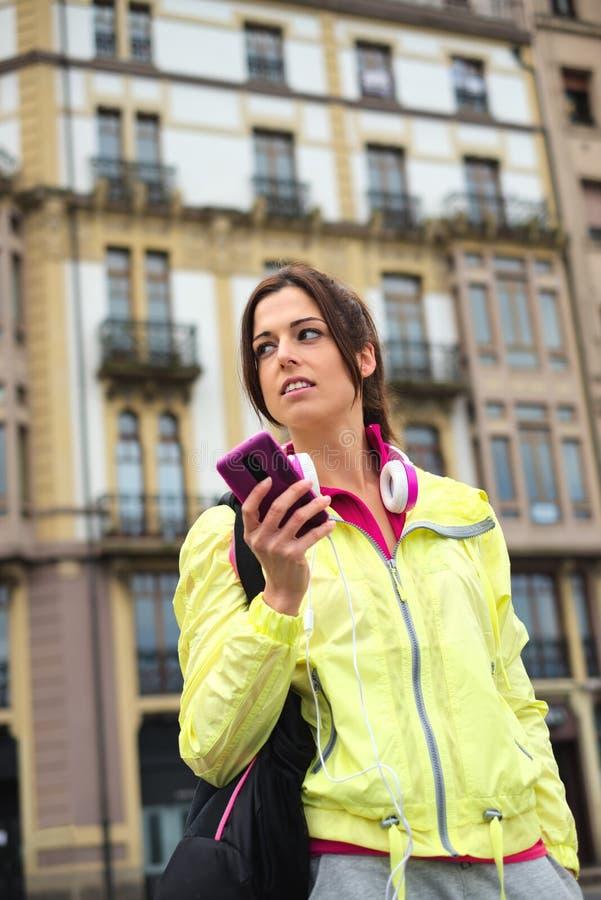 Sportief stedelijk vrouwen texting bericht op smartphone in straat stock afbeelding