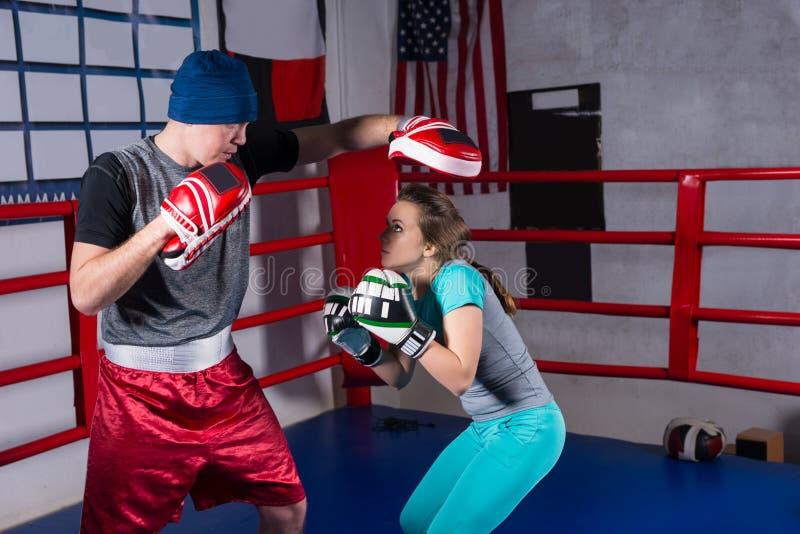 Sportief wijfje die kickboxing opleiding met haar bus doen stock foto