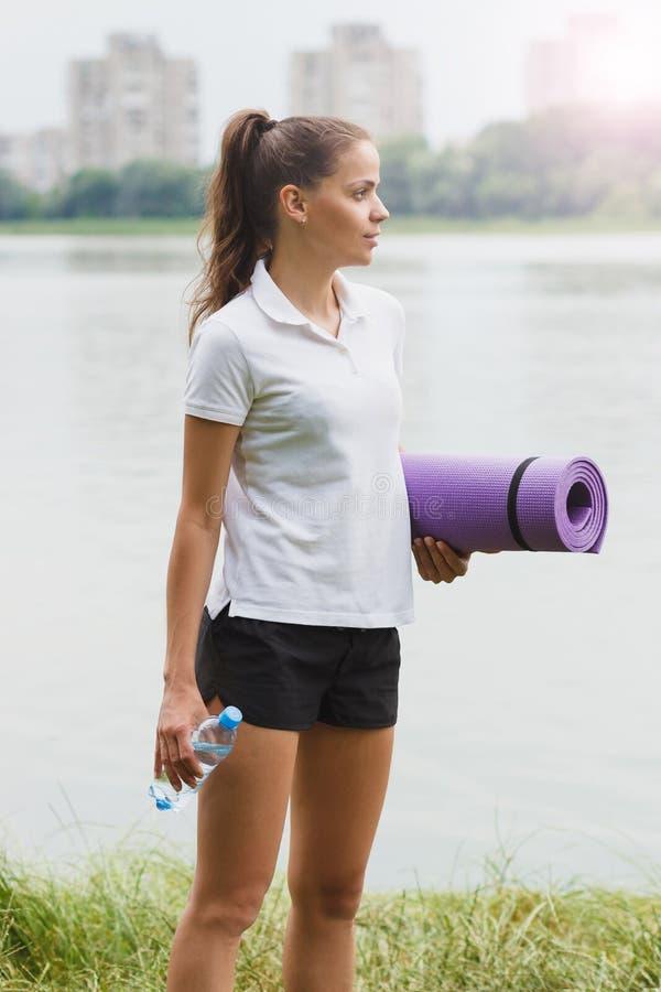 Sportieve aantrekkelijke vrouw op de merenkust met een mat en fles met water royalty-vrije stock afbeelding