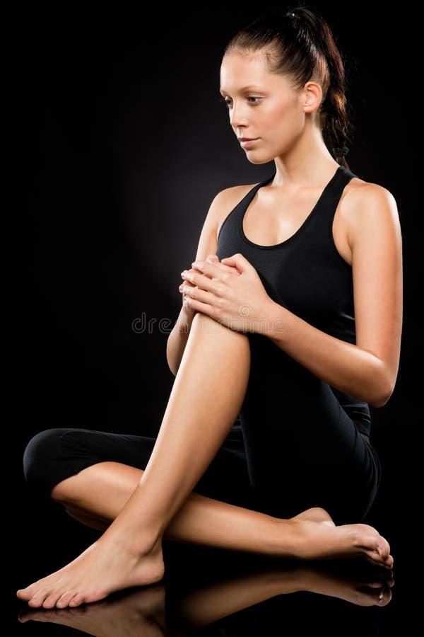 Sportieve donkerbruine vrouw die terwijl het doen van yoga ontspannen stock afbeeldingen