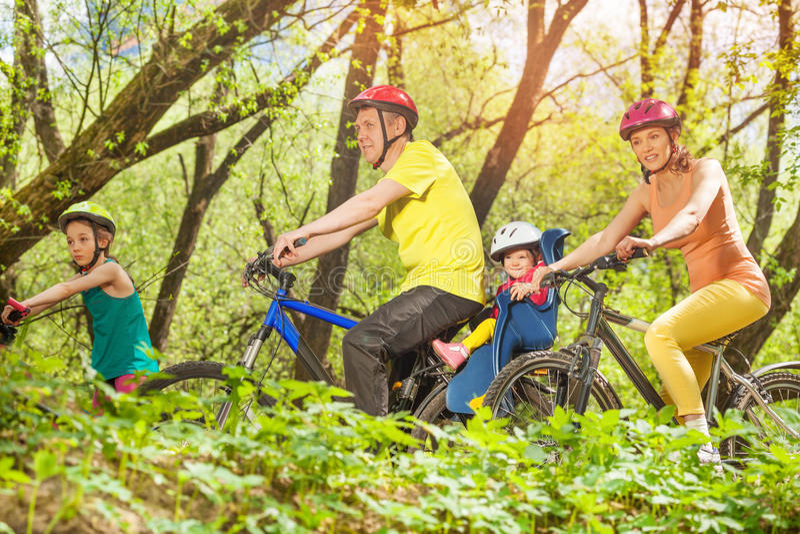 Sportieve familie lopende fietsen in het zonnige bos stock afbeelding