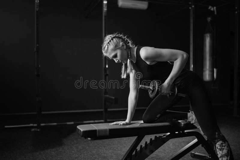 Sportieve geschikte vrouwenbodybuilder in gymnastiek opheffende domoren op bank Rebecca 36 De ruimte van het exemplaar stock afbeelding