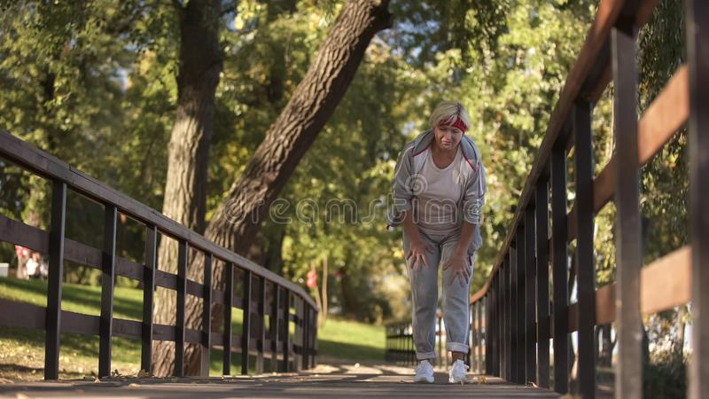 Sportieve hogere dame die haar knie houden die scherpe pijn voelen tijdens jogging, gezondheid stock afbeeldingen