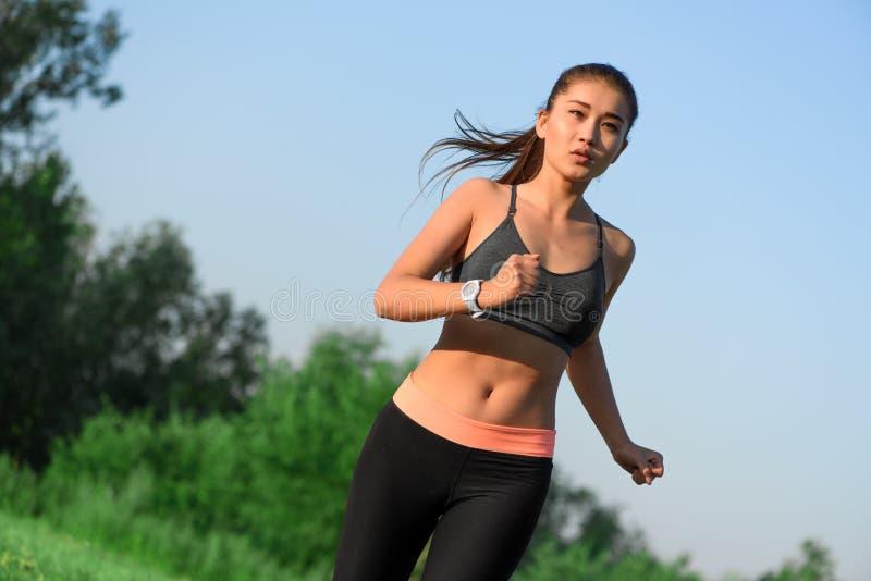 Sportieve jonge Aziatische vrouwenjogging bij park stock fotografie