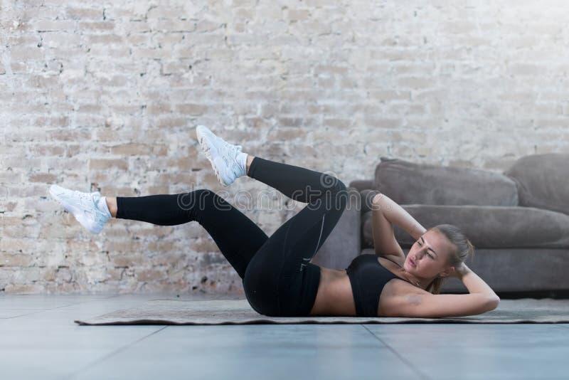 Sportieve jonge dame die kruiselingse krakenoefening doen die op een deken bij moderne studio liggen stock fotografie