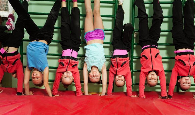 Sportieve jonge geitjes die handstandpositie in gymnastiek maken royalty-vrije stock foto's