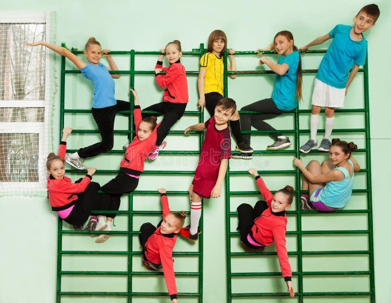 Sportieve jonge geitjes die pret op muur opgezette gymnastiekladder hebben royalty-vrije stock foto's